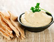 Bowl of fresh hummus dip with pita bread slices